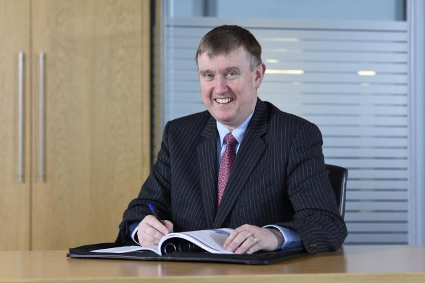 Finance Minister Mervyn Storey at desk