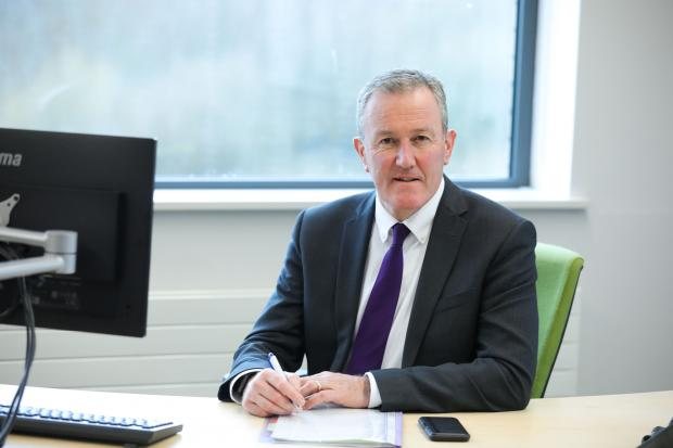 Finance Minister Conor Murphy sitting at his desk, looking to camera.