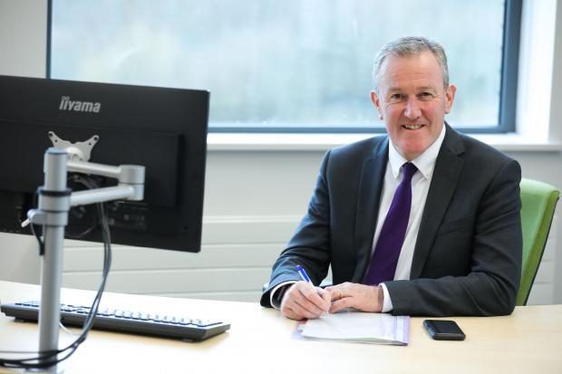 Finance Minister Conor Murphy sitting at his desk, smiling to camera.